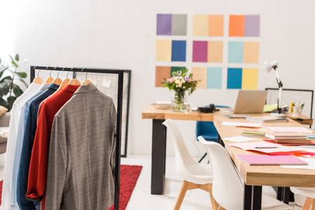 fashionable clothes on hangers,  paperwork on table in modern office with color palette on wall 写真素材 - 111858529