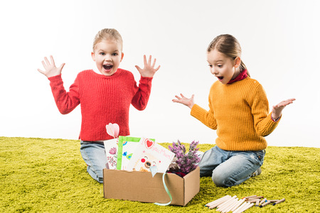 excited little sisters with box of materials for art sitting on floor isolated on white 免版税图像