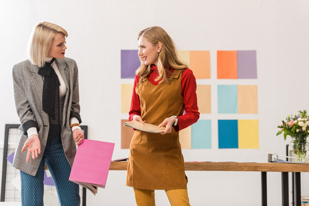 fashionable magazine editors working in modern office with color palette on wall Stockfoto