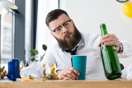 portrait of businessman in formal wear with bottle of champagne at workplace in office