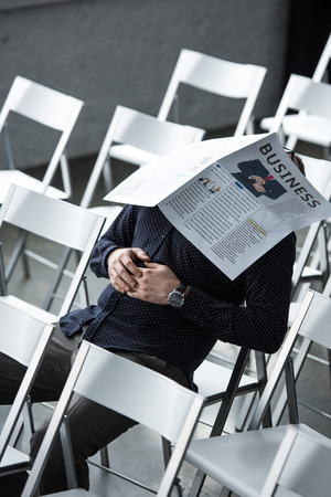 partial view of businessman sleeping with newspaper on face while sitting in meeting room Stock Photo