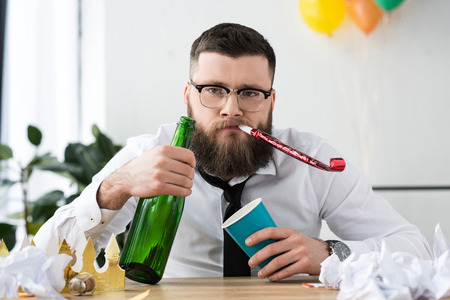 portrait of businessman in formal wear with bottle of champagne at workplace in office 写真素材 - 111859255