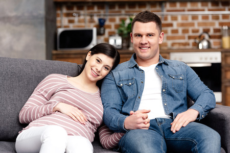 happy young pregnant couple sitting together on couch and smiling at camera