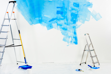 ladders and paint roller brushes in blue paint 写真素材 - 111858981
