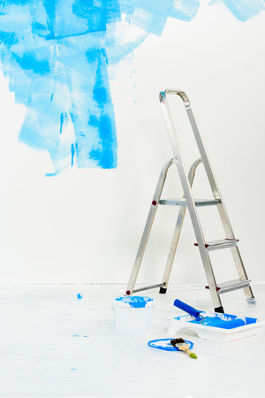 ladder and paint roller brush in blue paint 写真素材