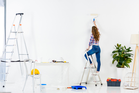rear view of girl standing on ladder and painting wall