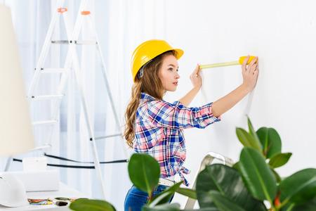 jeune femme, mesurer, mur, à, mètre ruban