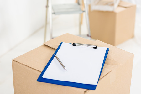 clipboard with pen on box in empty room