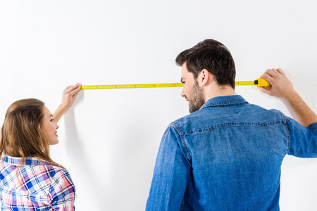 girlfriend and boyfriend measuring wall with tape measure 版權商用圖片 - 111859495