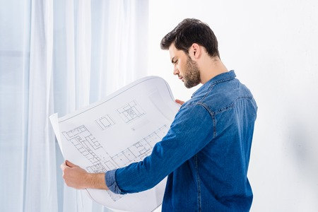 handsome man looking at blueprint on white Banco de Imagens