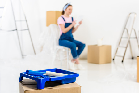 girl sitting with packed boxes in new house with paint tray on foreground