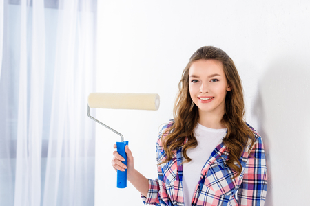 smiling girl holding paint roll brush and looking at camera