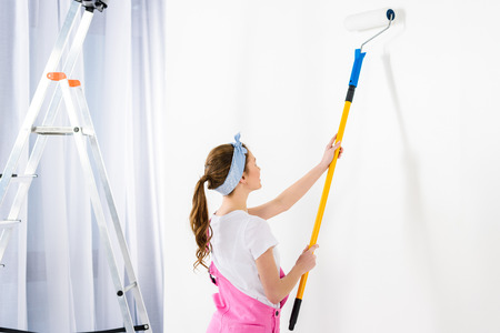 girl painting wall with white paint