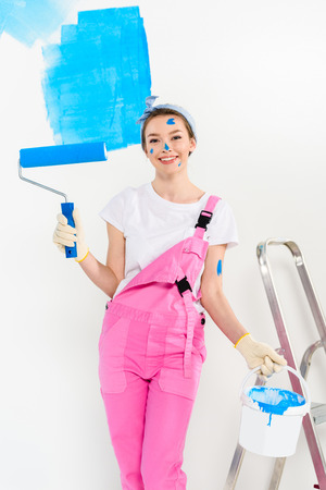 smiling girl standing with paint roller brush and looking at camera