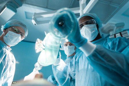 Ansicht von unten des afroamerikanischen Anästhesisten, der eine Sauerstoffmaske über dem Patienten hält