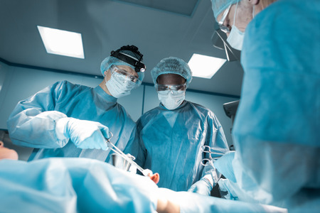 bottom view of multicultural surgeons and patient in operating room