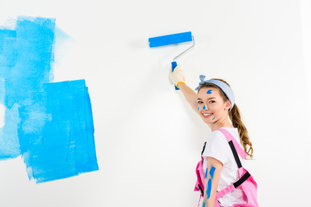 smiling girl painting wall with blue paint