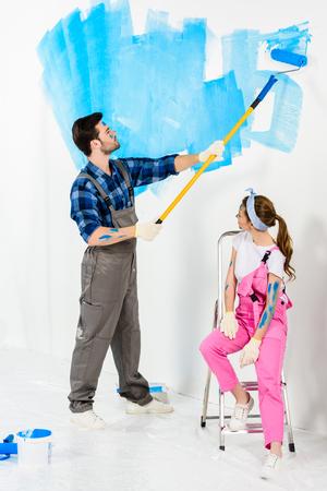 boyfriend painting wall and girlfriend sitting on ladder
