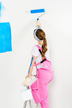 rear view of girl painting wall with blue paint Banco de Imagens