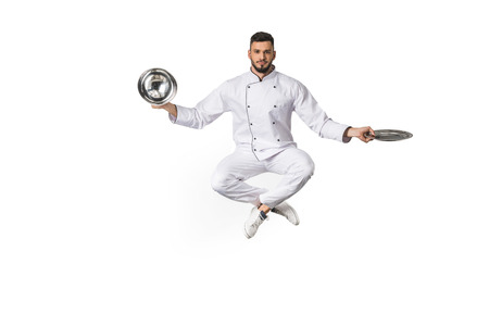 young male chef with plates jumping and looking at camera isolated on white