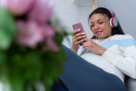 african american pregnant woman listening music with headphones and using smartphone