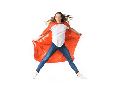 young woman in red mantle jumping and looking at camera isolated on white Banco de Imagens