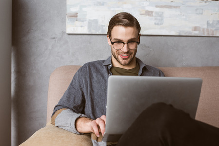 happy young businessman working with laptop on couch Banque d'images