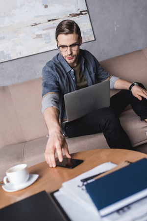 young handsome man with laptop reaching for smartphone