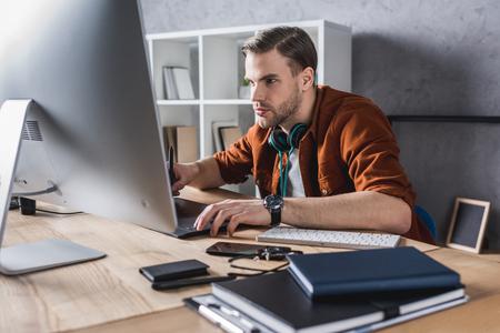 beau jeune homme travaillant avec un ordinateur au bureau moderne