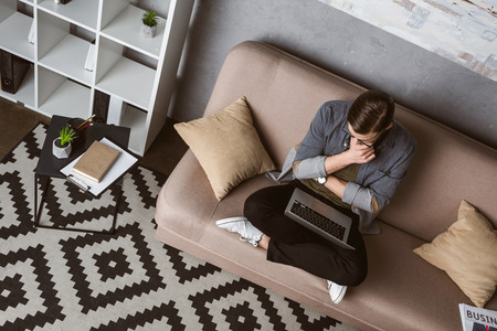 high angle view thoughtful freelancer working with laptop while sitting on couch Banque d'images