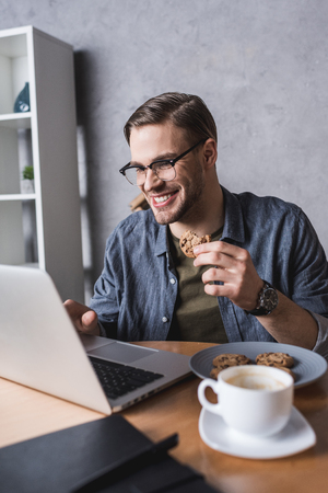 young handsome man working with laptop and eating cookies Banque d'images