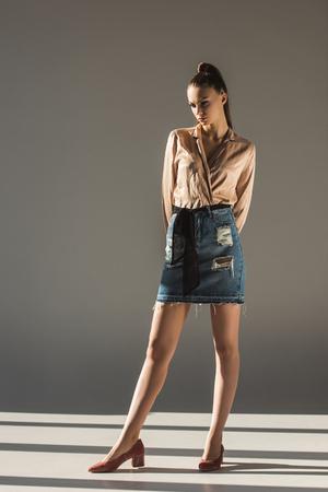 beautiful stylish girl posing in blouse and denim skirt