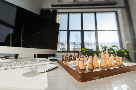 close-up shot of chess board at workplace with computer