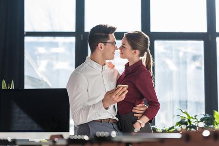 Besos atractivos jóvenes empresarios en ropa formal con romance de oficina