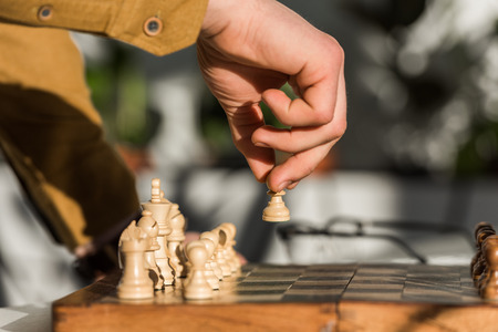 cropped shot of man making move while playing chess