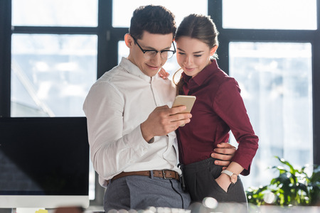attractive young businesspeople in formal clothing having office romance and using smartphone together Reklamní fotografie