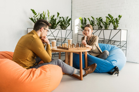 young focused couple playing chess while sitting on beanbags