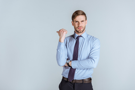 Young unsatisfied businessman pointing isolated on grey Stock Photo