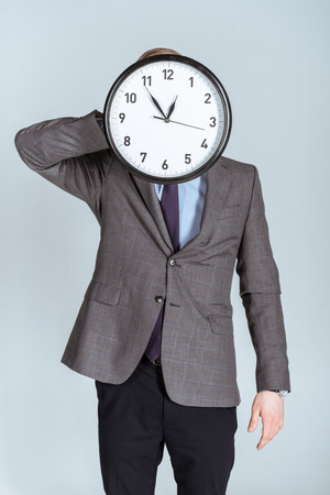 Businessman in suit holding clock over his face isolated on grey Stock fotó