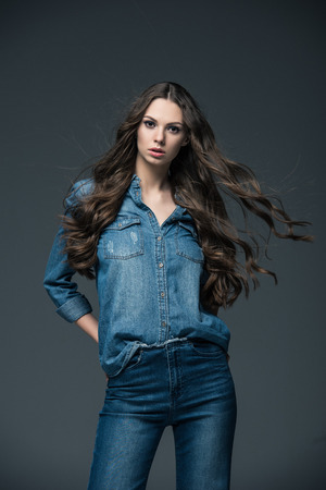 attractive girl with long hair posing in jeans, isolated on grey