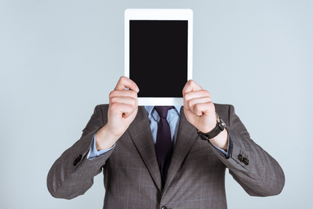 Businessman holding digital tablet over his face isolated on grey Stock fotó