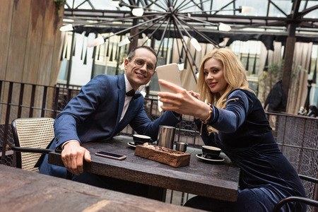 beautiful adult couple taking selfie at restaurant