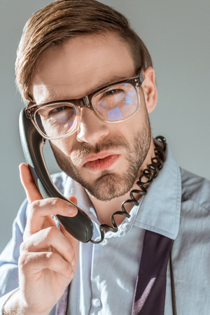 Close-up view of dissatisfied businessman talking on the phone isolated on grey