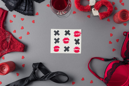 top view of tic-tac-toe game between underwear and glass of wine