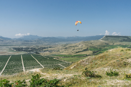 Parachutist gliding in blue sky over scenic landscape of Crimea, Ukraine, May 2013 Imagens - 111951106