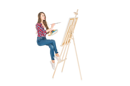 young woman levitating and painting on easel isolated on white