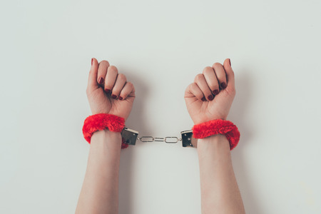 cropped image of woman hands in red fluffy handcuffs on white Stock Photo - 111950855