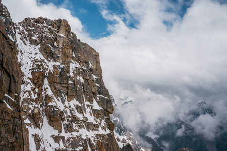 view of rocky slope with snow against clouds in sky, Ala Archa National Park, Kyrgyzstan 版權商用圖片