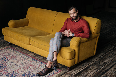 fashionable elegant man sitting on yellow couch Stock Photo
