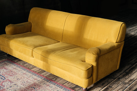 yellow couch on wooden floor with carpet 스톡 콘텐츠 - 111951684